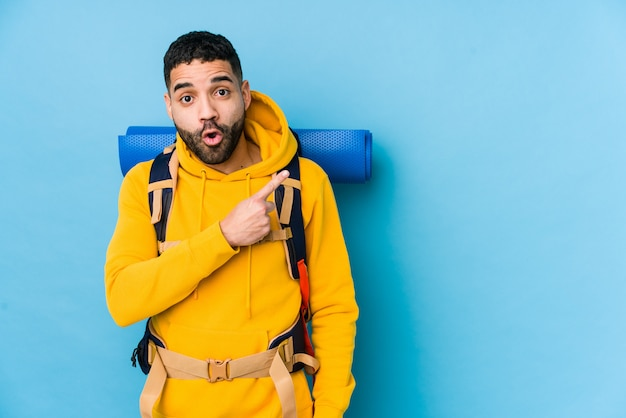 Młody Arabski Podróżnika Backpacker Mężczyzna Odizolowywał Wskazywać Strona Premium Zdjęcia