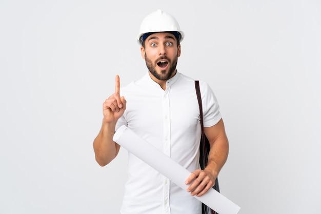 Młody Architekta Mężczyzna Z Hełmem I Trzymający Projekty Odizolowywający Na Biel ścianie Myśleć Pomysł Wskazuje Palec Up Premium Zdjęcia