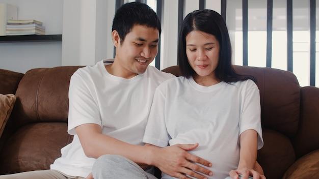 Młody Asian Para W Ciąży Mężczyzna Dotknąć Brzucha żony Rozmawiać Z Dzieckiem. Mama I Tata Czują Się Szczęśliwi, Uśmiechając Się Spokojnie, Jednocześnie Dbając O Dziecko, Ciąża Leży Na Kanapie W Salonie W Domu. Darmowe Zdjęcia