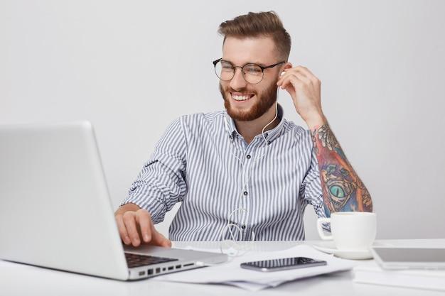 Młody Atrakcyjny Biznesmen Ma Szczęśliwy Wyraz, Odpoczywa Po Ciężkiej Pracy, Słucha Muzyki Lub Ogląda Film Przez Słuchawki I Laptop. Wytatuowany Student Hipster Cieszy Się Ulubionym Dźwiękiem Darmowe Zdjęcia