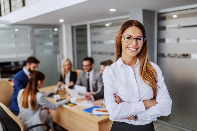 Młody Atrakcyjny Kaukaski Businesswoman W Wizytowym Stojących W Sali Konferencyjnej Z Rękami Skrzyżowanymi I Patrząc Na Kamery. W Tle Są Jej Koledzy Pracujący Nad Projektem. Premium Zdjęcia