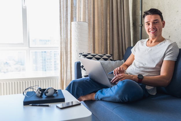 Młody Atrakcyjny Mężczyzna Siedzi Na Kanapie W Domu, Pracując Na Komputerze Przenośnym W Trybie Online, Za Pomocą Internetu Darmowe Zdjęcia