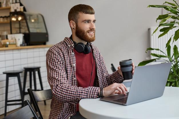 Młody Atrakcyjny Rudy Brodaty Mężczyzna Pracuje Przy Laptopie, Siedzi W Kawiarni I Pije Kawę, Szeroko Uśmiechając Się I Ciesząc Się Z Pracy, Odwracając Wzrok W Oczekiwaniu Na Sukces, Nosząc Podstawowe Ubrania. Darmowe Zdjęcia