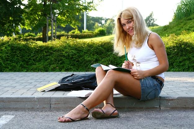 Młody atrakcyjny uczeń czyta książkę Darmowe Zdjęcia