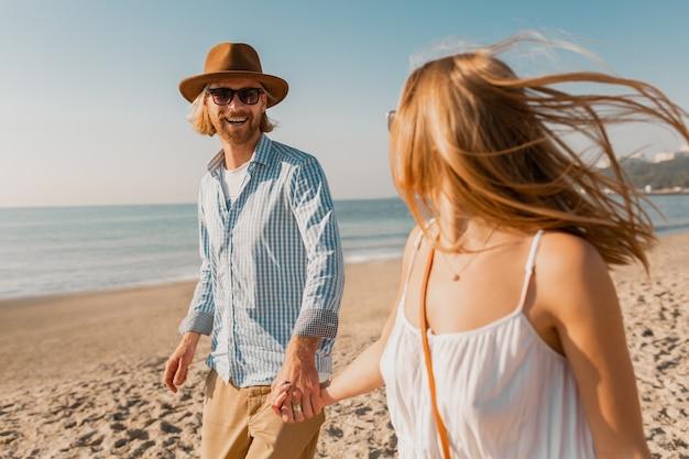 Młody Atrakcyjny Uśmiechnięty Szczęśliwy Mężczyzna W Kapeluszu I Blond Kobieta W Białej Sukni Działa Razem Na Plaży Darmowe Zdjęcia