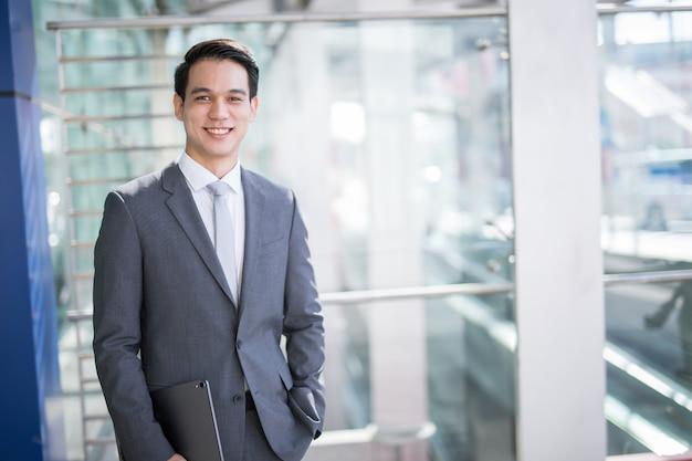 Młody azjatycki biznesowy mężczyzna trzyma pastylkę Premium Zdjęcia