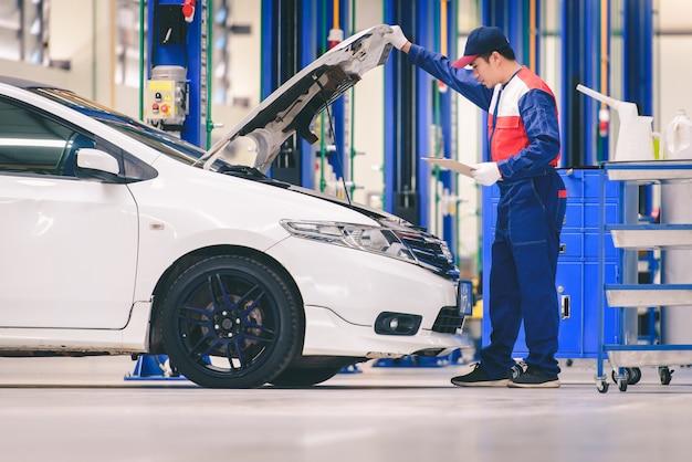 Młody Azjatycki Mechanik Samochodowy W Warsztacie Samochodowym Analizuje Problemy Z Silnikiem I Sprawdza Silnik Premium Zdjęcia