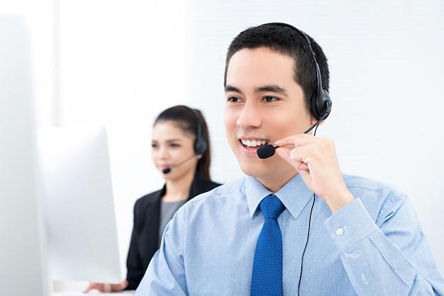Młody azjatycki męski telemarketingowy obsługa klienta agent pracuje w centrum telefonicznym Premium Zdjęcia