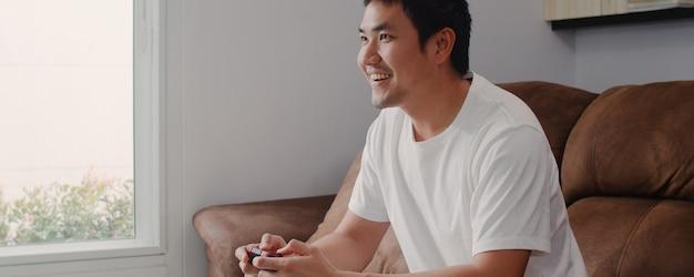 Młody azjatycki mężczyzna używa joystick bawić się wideo gry w telewizi w żywym pokoju, męski czuć szczęśliwy używać relaksuje czasu lying on the beach na kanapie w domu. mężczyźni grają w gry relaks w domu. Darmowe Zdjęcia