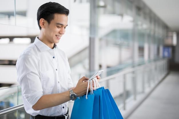 Młody azjatycki mężczyzna z torba na zakupy używa telefon komórkowego i ono uśmiecha się podczas gdy robić zakupy Premium Zdjęcia