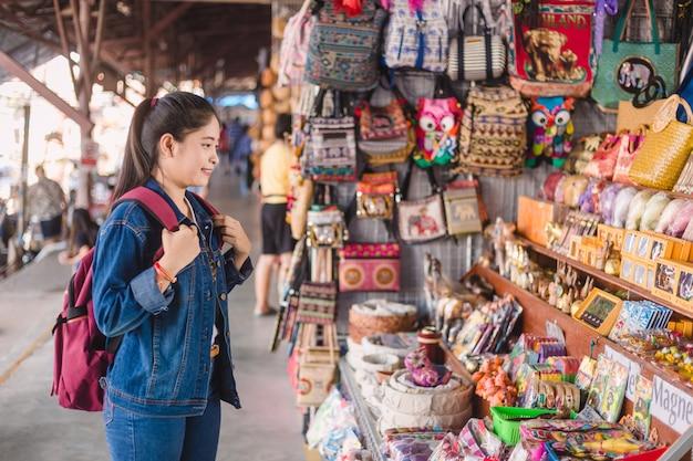 Młody azjatykci dziewczyny odprowadzenie przy dumonoe saduak spławowym rynkiem, tajlandia Premium Zdjęcia