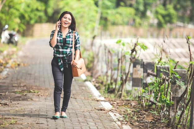 Młody Azjatykci Kobiety Mówienie Na Telefonie Podczas Gdy Chodzący Na Równi Premium Zdjęcia