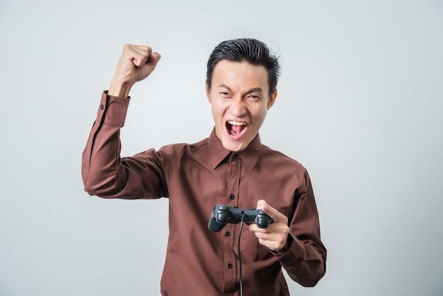 Młody Azjatykci Mężczyzna Bawić Się Wideo Grę Z Joystickiem, Szczęśliwy Uczucie. Premium Zdjęcia