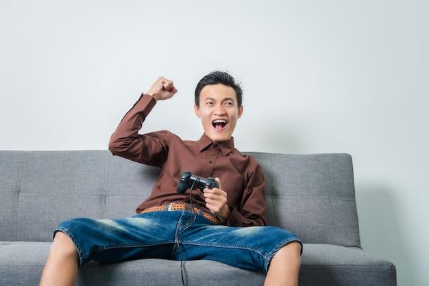 Młody Azjatykci Mężczyzna Mienia Joystick Dla Bawić Się Piłki Nożnej Wideo Grę Podczas Gdy Siedzący Na Kanapie W żywym Pokoju. Premium Zdjęcia