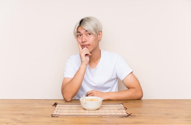 Młody azjatykci mężczyzna z ramen w stołowym główkowaniu pomysł Premium Zdjęcia