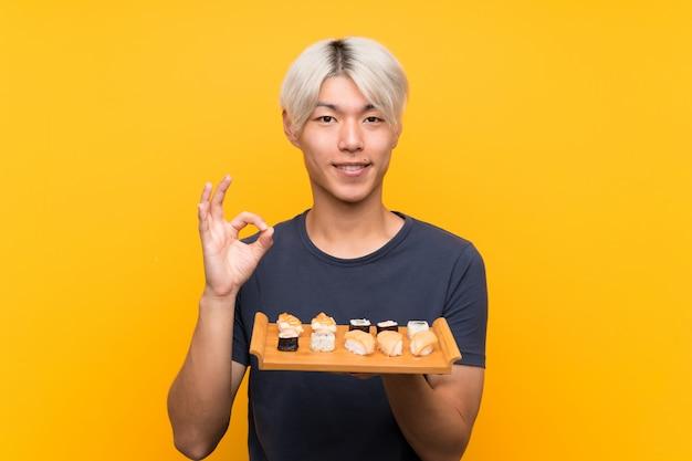 Młody Azjatykci Mężczyzna Z Suszi Nad Odosobnionym Kolorem żółtym Pokazuje Ok Znaka Z Palcami Premium Zdjęcia