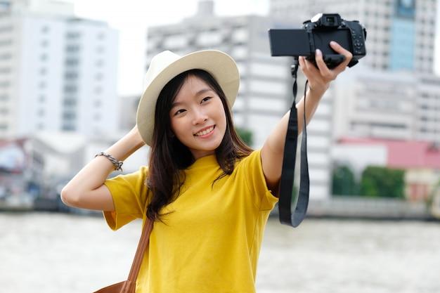 Młody azjatykci żeński podróżnik bierze selfie fotografię w mieście outdoors Premium Zdjęcia