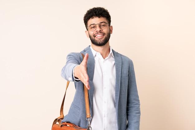 Młody Biznes Marokański Mężczyzna Na Białym Tle Na Beż Drżenie Rąk Za Zamknięcie Dobrej Oferty Premium Zdjęcia