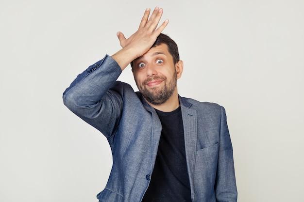 Młody Biznesmen Człowiek Z Brodą W Kurtce, Z Wyrazem Frustracji I Nieporozumień. Zaskoczony, Kładąc Rękę Na Głowie Za Błąd. Premium Zdjęcia