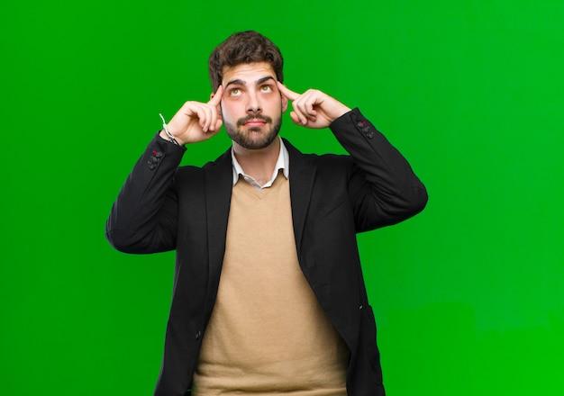 Młody Biznesmen Czuje Się Zdezorientowany Lub Wątpiąc, Koncentrując Się Na Pomysł, Ciężko Myśląc, Patrząc, Aby Skopiować Przestrzeń Po Stronie ścianę Zielony Premium Zdjęcia
