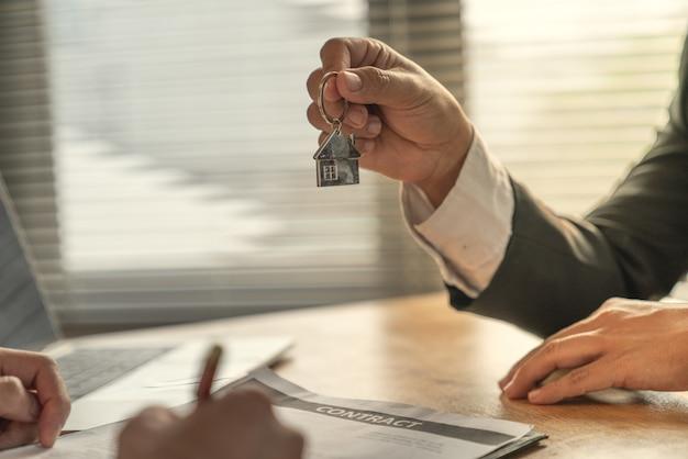 Młody biznesmen i klient nabywcy domu wspólnie osiągnęli docelowe środki i podpisali umowę. Premium Zdjęcia