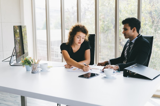 Młody biznesmen i kobieta dyskutuje o biznesie na dane prześcieradłach w ministerstwie spraw wewnętrznych Premium Zdjęcia
