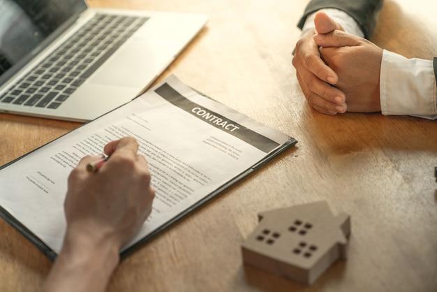 Młody biznesmen i nabywca domu osiągnęli wspólnie cel i podpisali umowę sprzedaży nieruchomości Premium Zdjęcia