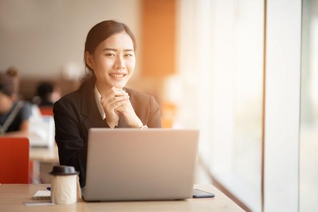 Młody biznesmen nosi czarny garnitur przy biurku. Premium Zdjęcia
