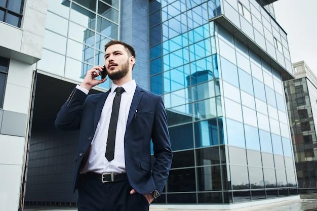 Młody Biznesmen Opowiada Na Telefonie Komórkowym Na Tle Szklany Biznesowy Budynek W Błękitnym Kostiumu Premium Zdjęcia