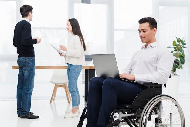Młody biznesmen siedzi na wózku inwalidzkim za pomocą laptopa z kolegą omawianie czegoś w tle Darmowe Zdjęcia