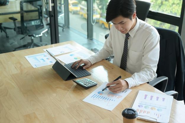 Młody Biznesmen Sprawdza Dane Na Wykresie I Używa Laptop Na Biurowym Biurku. Premium Zdjęcia