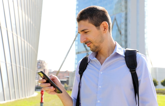 Młody Biznesmen Sprawdzanie Swojego Telefonu Komórkowego W Nowoczesnym Mieście Premium Zdjęcia