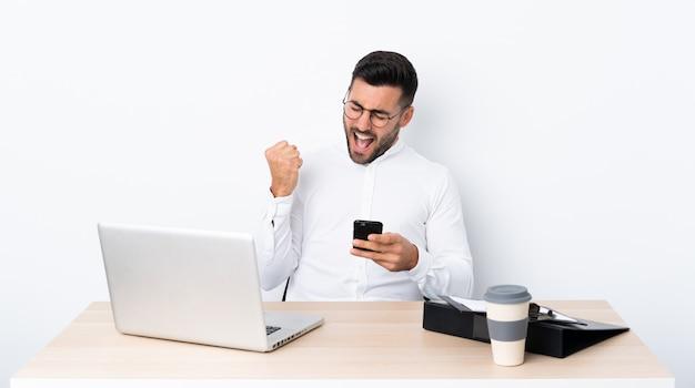 Młody Biznesmen W Miejscu Pracy Z Telefonem W Zwycięstwo Pozyci Premium Zdjęcia