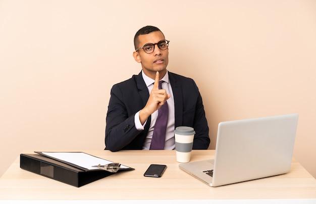 Młody Biznesmen W Swoim Biurze Z Laptopem I Inne Dokumenty Sfrustrowane I Wskazując Na Przód Premium Zdjęcia