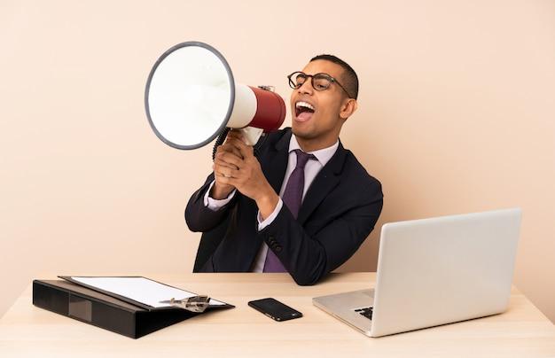 Młody Biznesmen W Swoim Biurze Z Laptopem I Innymi Dokumentami Krzyczy Przez Megafon Premium Zdjęcia