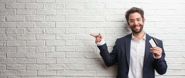 Młody biznesowy mężczyzna jest ubranym kostium przeciw białej cegły ścianie wskazuje na stronę Premium Zdjęcia