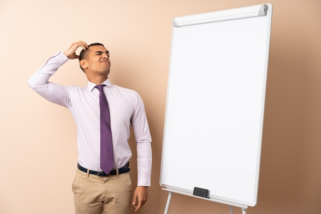 Młody Biznesowy Mężczyzna Nad Odosobnioną ścianą Daje Prezentaci Na Białej Desce I Ma Wątpliwości Z Zmieszanym Twarzy Wyrażeniem Premium Zdjęcia
