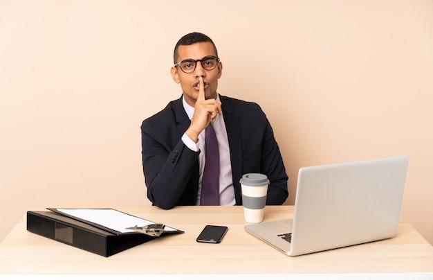 Młody Biznesowy Mężczyzna W Jego Biurze Z Laptopem I Innymi Dokumentami Pokazuje Znaka Cisza Gesta Kładzenia Palec W Usta Premium Zdjęcia