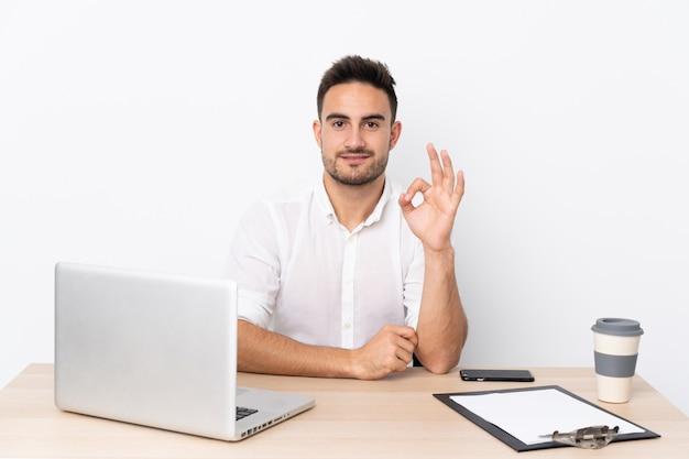 Młody Biznesowy Mężczyzna Z Telefonem Komórkowym W Miejscu Pracy Pokazuje Ok Znaka Z Palcami Premium Zdjęcia