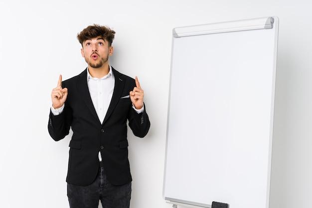 Młody Biznesowy Trenowanie Mężczyzna Wskazuje Do Góry Z Rozpieczętowanym Usta Premium Zdjęcia