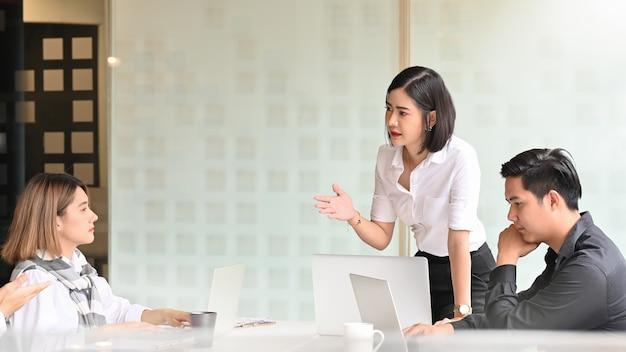 Młody bizneswoman teraźniejszy w pokoju konferencyjnym. Premium Zdjęcia