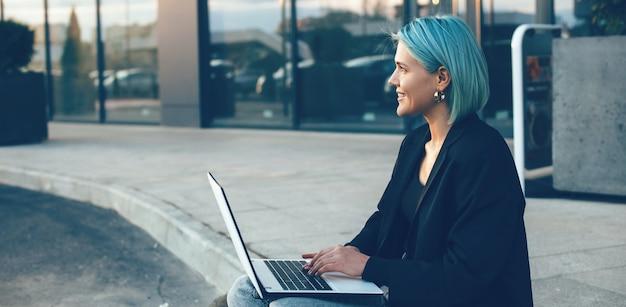 Młody Bizneswoman Z Niebieskimi Włosami Siedzi Na Ulicy I Pracuje Na Laptopie Premium Zdjęcia