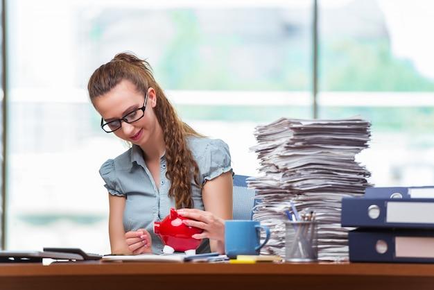 Młody bizneswoman z prosiątko bankiem w biurze Premium Zdjęcia