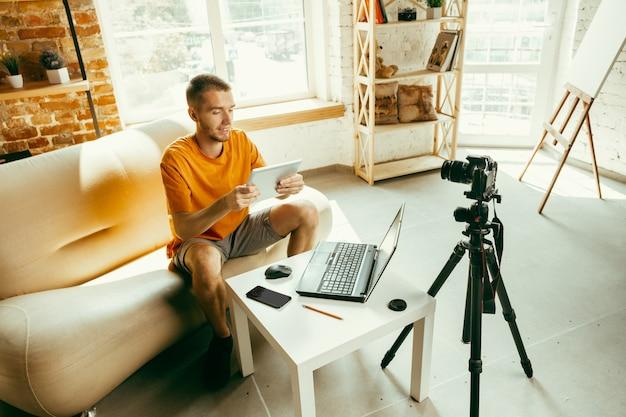 Młody Bloger Kaukaski Z Profesjonalnym Aparatem Nagrywającym Recenzję Wideo Tabletu W Domu Darmowe Zdjęcia