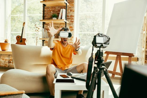 Młody Bloger Kaukaski Z Profesjonalnym Sprzętem Nagrywający W Domu Przegląd Wideo Okularów Vr. Blogowanie, Videoblog, Vlogowanie. Mężczyzna Korzystający Z Zestawu Słuchawkowego Wirtualnej Rzeczywistości Podczas Przesyłania Strumieniowego Na żywo. Darmowe Zdjęcia