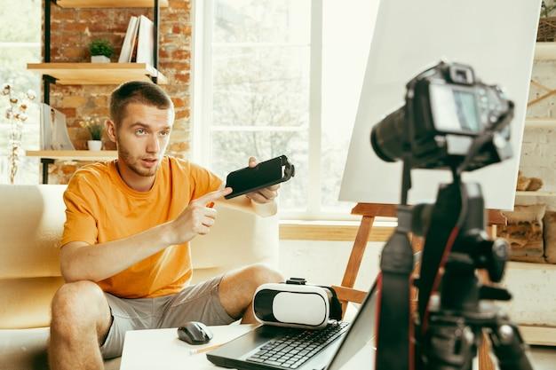 Młody Bloger Kaukaski Z Profesjonalnym Sprzętem Nagrywający W Domu Przegląd Wideo Okularów Vr. Blogowanie, Videoblog, Vlogowanie. Mężczyzna Ocenia Zestaw Słuchawkowy Rzeczywistości Wirtualnej Podczas Transmisji Na żywo. Darmowe Zdjęcia