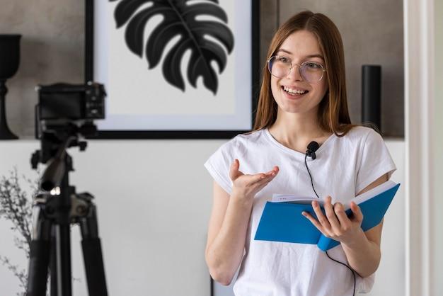 Młody Blogger Nagrywa Z Profesjonalnym Aparatem Trzymającym Książkę Darmowe Zdjęcia