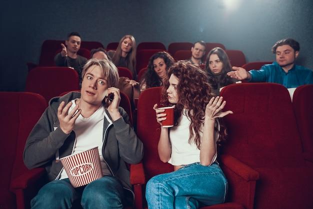Młody Blondyn Mówi Przez Telefon Podczas Pokazu Filmowego. Premium Zdjęcia