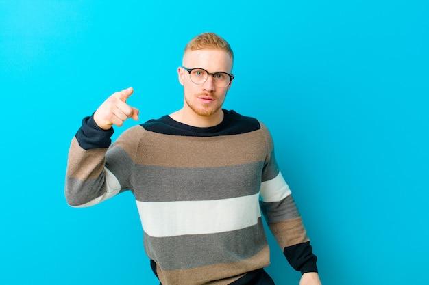 Młody Blondyn Wskazujący Na Aparat Z Gniewnym, Agresywnym Wyrazem, Wyglądający Jak Wściekły, Szalony Szef Premium Zdjęcia