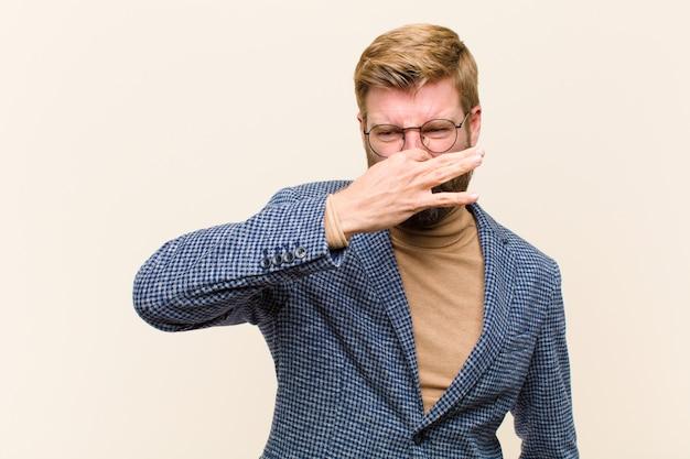 Młody Blondynka Biznesmen Czuje Się Zniesmaczony, Trzymając Nos, Aby Uniknąć Zapachu Faul I Nieprzyjemnego Smrodu Premium Zdjęcia